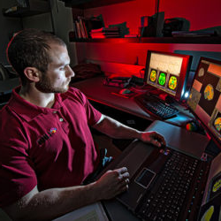 a student sits in a dark lab, MRI brain scans on computer screens light his face. a gentle red glow surrounds the background