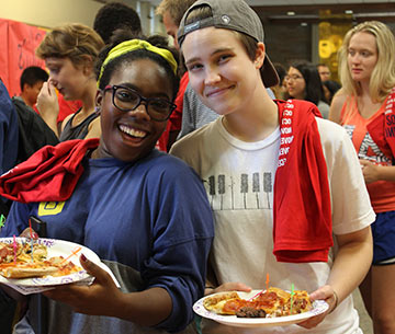 two students holding plates of food, smiling