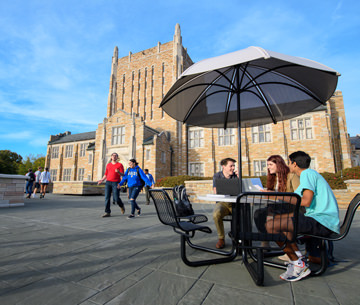 students sitting at a table on the plaza in front of McFarlin library