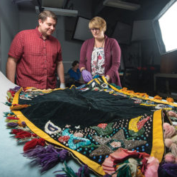 students studying exhibit that features a colorful textile at a museum