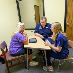 a student and professor consult with an adult in an observed setting within the Mary K Chapman center