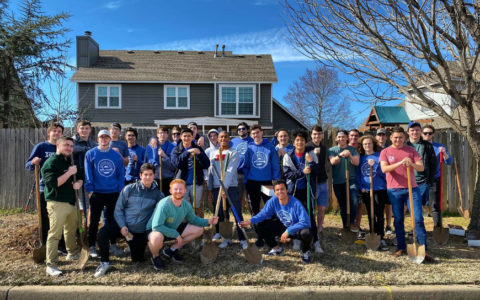 A large group of Kappa Sigma fraternity members standing outdoors holding shovels
