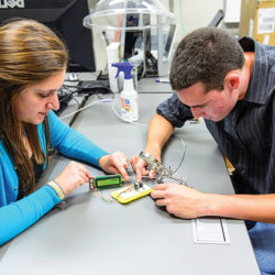 two students sit at a table, carefully adjusting the wiring of a small component