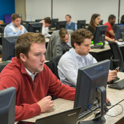 a group of students in the computer lab on campus in a business class working on an assignment