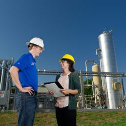 Two people in hard hats confer on a refinery site