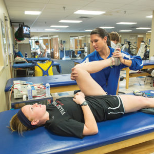 "a student performs knee exercises on a ""patient"" laying on a flat top treatment bed"