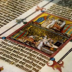 close up look of a medieval book with calligraphy and drawings