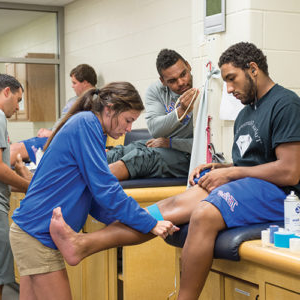 students practice bandaging knee injuries on fellow classmates
