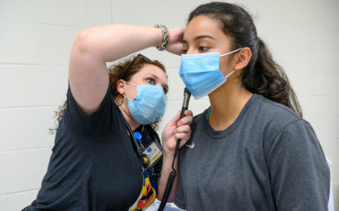 A family nurse practitioner student examining the ear of a high school student