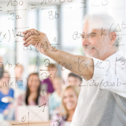 an instructor is seen through a clear dry erase board, covered in equations, while students take notes in the background